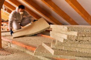 A worker insulating an attic